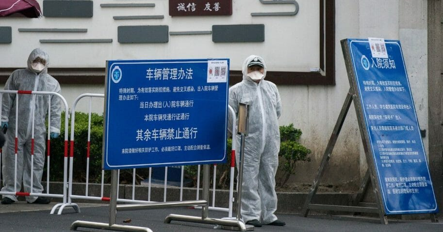 Workers wear protective masks and protective suits near the vehicle entrance of a hospital in Shanghai on March 2, 2020.