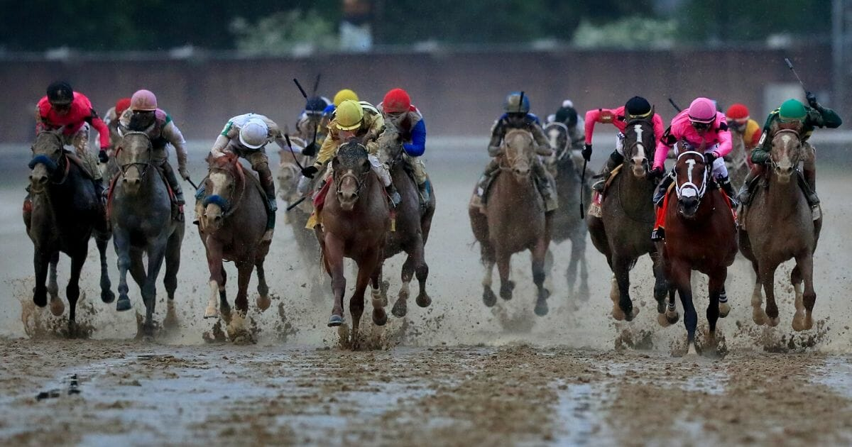 Country House, in yellow, races Maximum Security, in pink, to the finish in the 145th running of the Kentucky Derby at Churchill Downs on May 4, 2019, in Louisville, Kentucky.