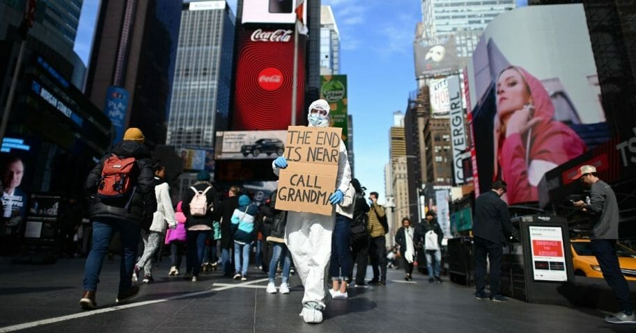 A man wearing a hazmat suit and a mask holds a sign at Times Square on March 14, 2020, in New York City.