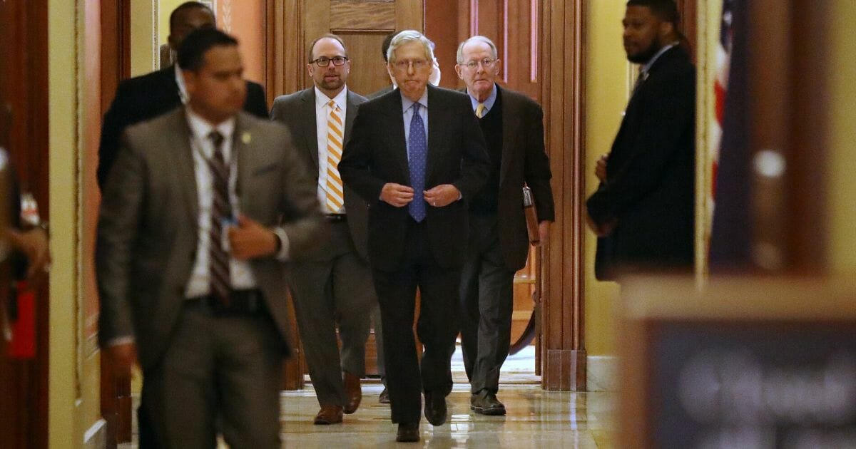 Senate Majority Leader Mitch McConnell of Kentucky, center, and Sen. Lamar Alexander of Tennessee, second from right, leave a meeting on the coronavirus relief package in the Capitol's Strom Thurmond Room on March 24, 2020.