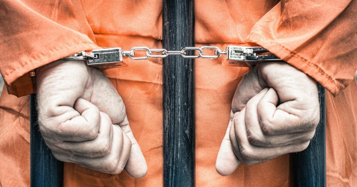 A stock photo of a prisoner is seen above.