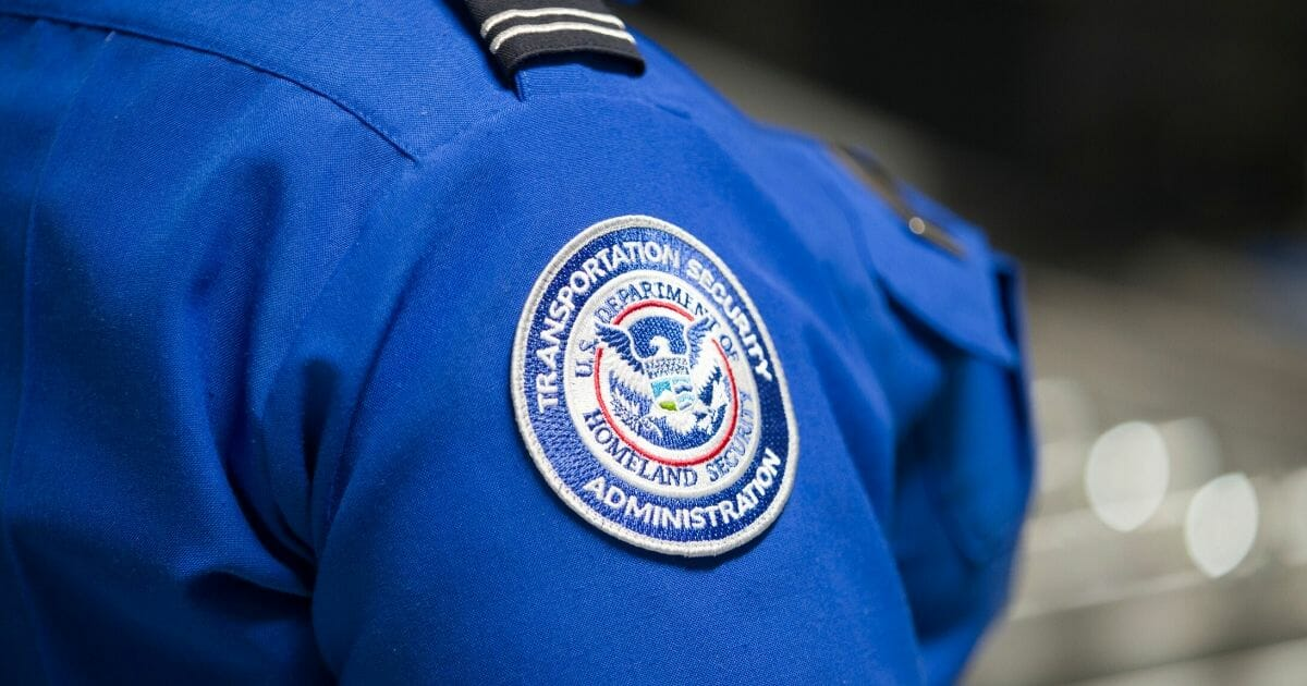 A Transportation Security Administration agent's patch is seen as she helps travelers place their bags through the 3-D scanner at the Miami International Airport on May 21, 2019, in Miami, Florida.