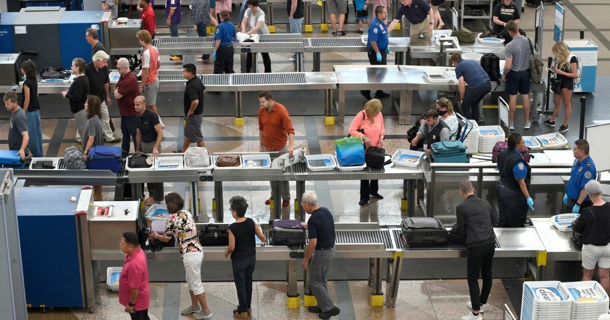 Airport passengers proceed through the TSA security checkpoint at the Denver International Airport in Colorado on Aug. 30, 2019.