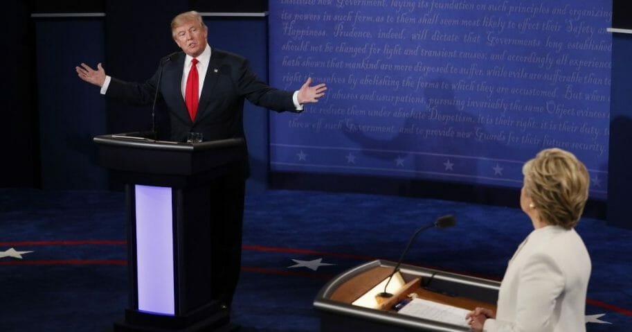 Republican presidential nominee Donald Trump speaks as Democratic presidential nominee Hillary Clinton looks on during the final presidential debate at the Thomas & Mack Center on the campus of the University of Las Vegas in Las Vegas on Oct. 19, 2016.
