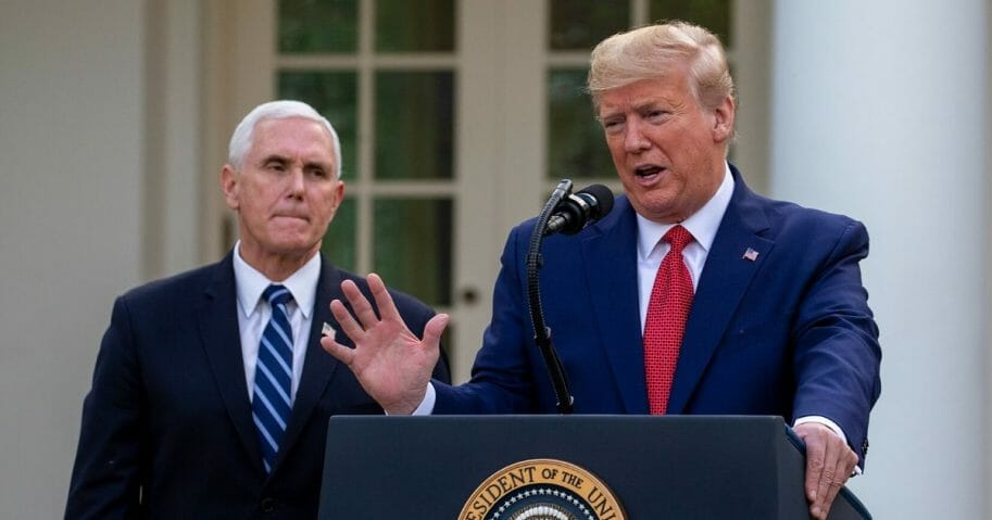 Vice President Mike Pence listens to President Donald Trump speak in the Rose Garden for the daily coronavirus briefing at the White House on March 29, 2020.