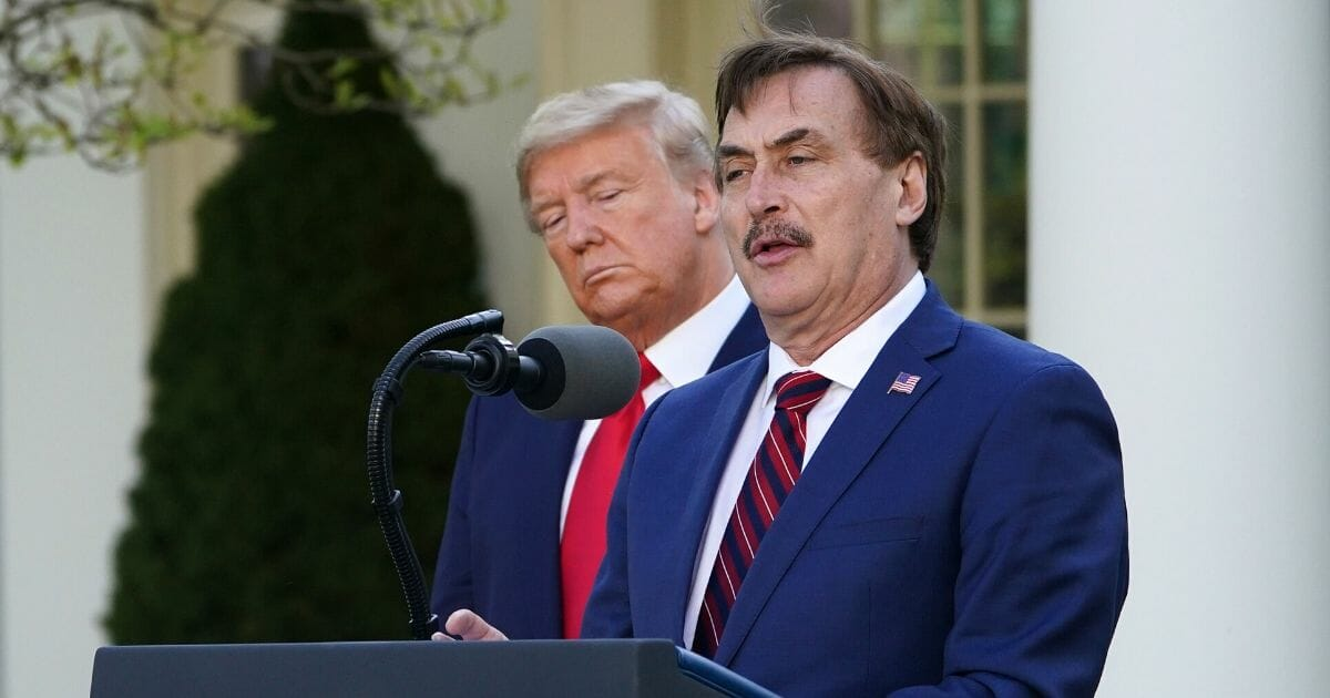 President Donald Trump listens as Mike Lindell, CEO of MyPillow, speaks during the daily briefing on the novel coronavirus in the Rose Garden of the White House on March 30, 2020.