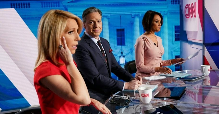 CNN news anchor Jake Tapper, center, flanked by Univision news anchor Ilia Calderón, right, watches as co-anchor Dana Bash adjusts her ear piece before the start of the 11th Democratic Party 2020 presidential debate with former Vice President Joe Biden and Vermont Sen. Bernie Sanders in a CNN Washington Bureau studio in Washington, D.C., on March 15, 2020.