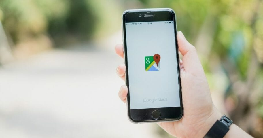 Stock image of a man holding a phone with the Google Maps app.