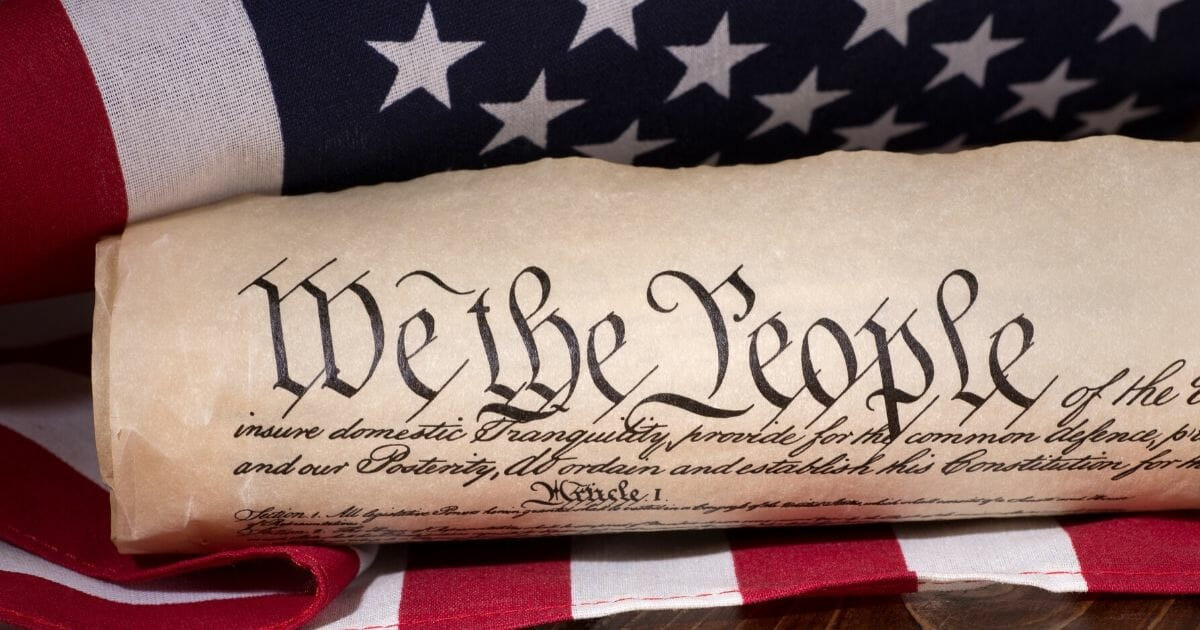 Stock image of the text of the preamble to the United States Constitution with an American flag in the background.