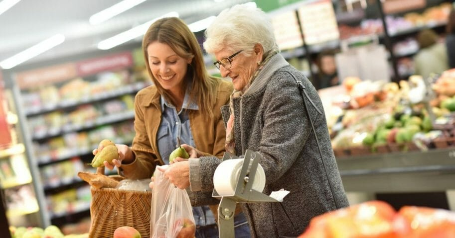 Stock image of an elderly woman with a younger woman at the grocery store.