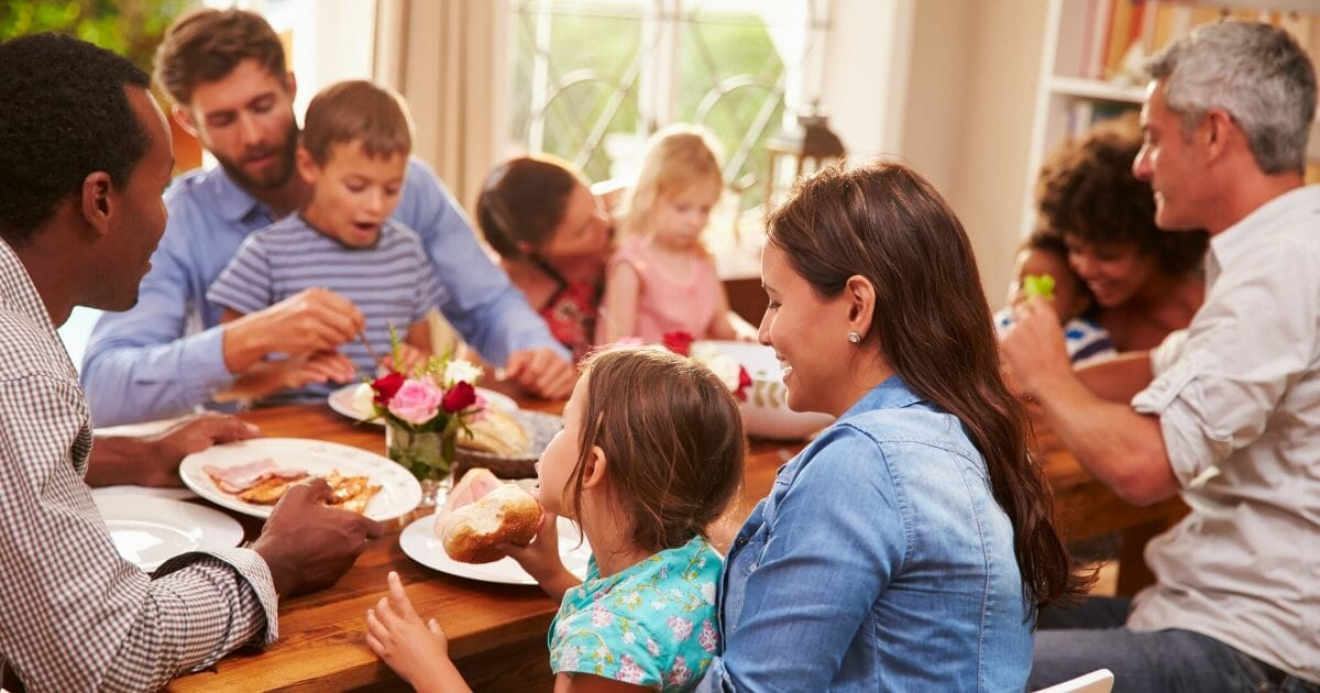 Stock image of family and friends sitting around a dinner table.