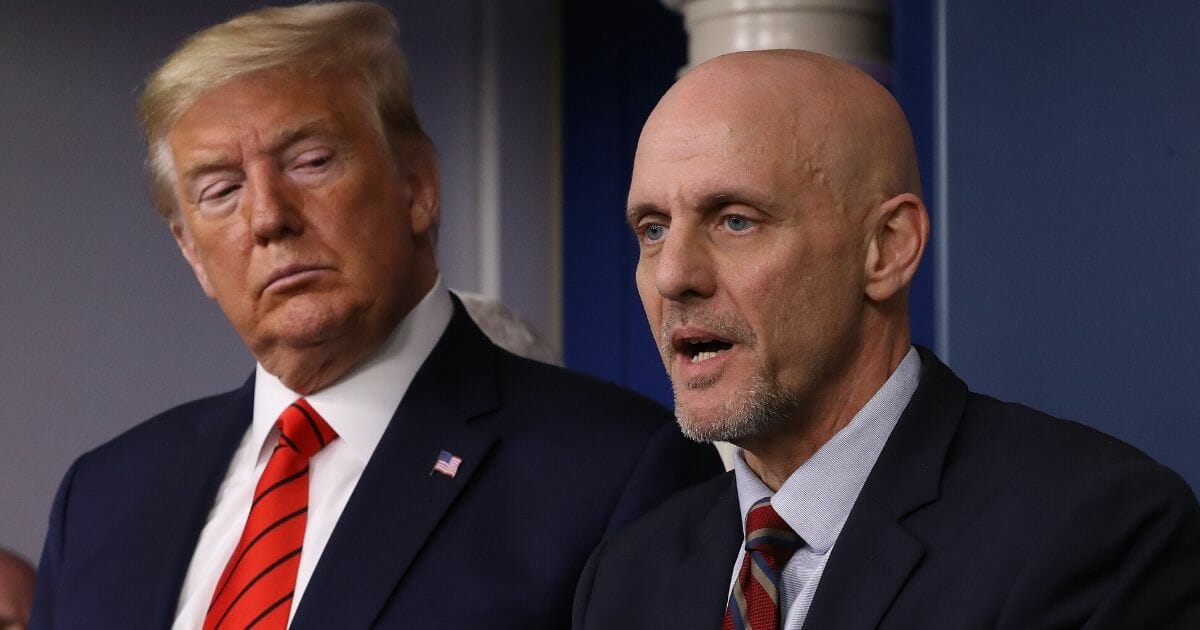 President Donald Trump listens to FDA Commissioner Stephen Hahn speak on the latest developments of the coronavirus outbreak in the James Brady Press Briefing Room at the White House on March 19, 2020, in Washington, D.C.
