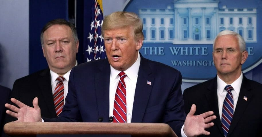 President Donald Trump speaks as Secretary of State Mike Pompeo, left, and Vice President Mike Pence listen during a news briefing on the latest development of the coronavirus outbreak in the U.S. at the James Brady Press Briefing Room at the White House on March 20, 2020, in Washington, D.C.