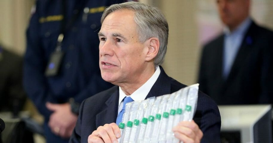 Texas Gov. Greg Abbott displays COVID-19 test collection vials as he addresses the media during a news conference held at Arlington Emergency Management on March 18, 2020, in Arlington, Texas.
