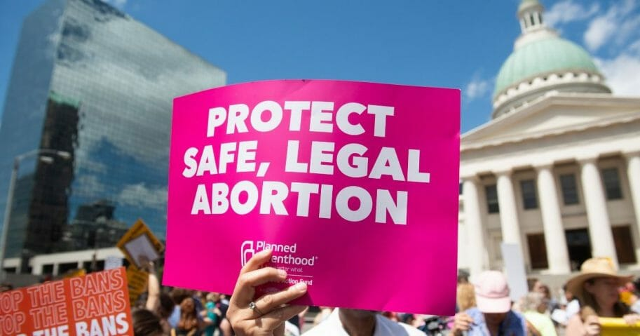 Protesters hold signs as they rally in support of Planned Parenthood near the Old Courthouse in St. Louis on May 30, 2019.