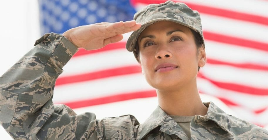 A female service member salutes in the stock image above.