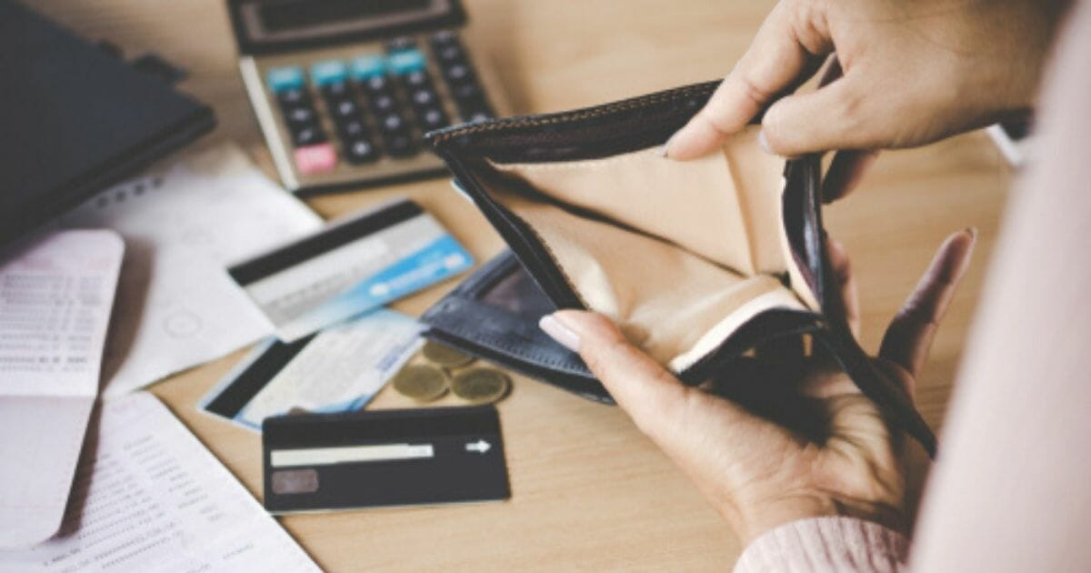 A woman is seen opening her wallet in the stock image above.