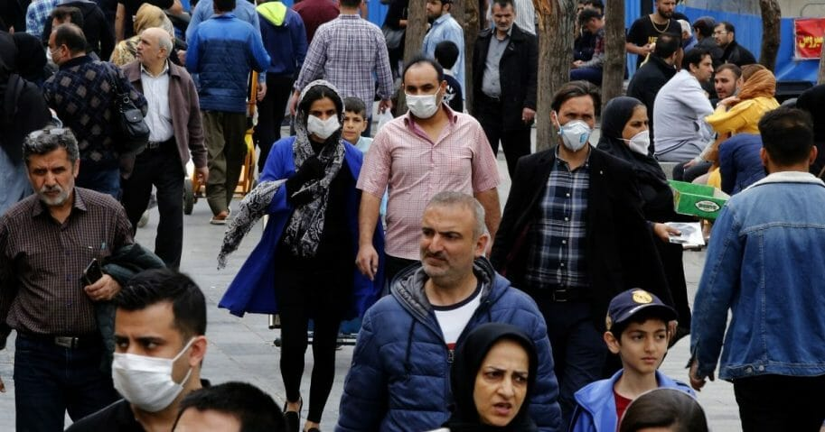 Iranians, some wearing protective masks, gather inside the capital city of Tehran's grand bazaar amid the COVID-19 coronavirus pandemic crisis on March 18, 2020.