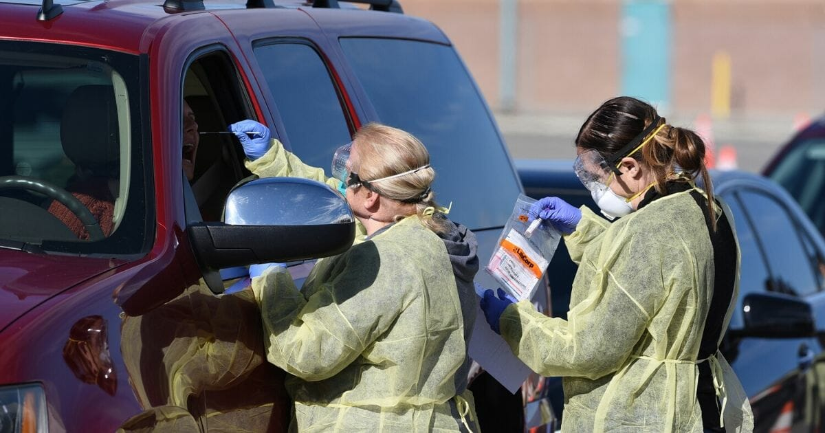 health care workers administering coronavirus tests in cars