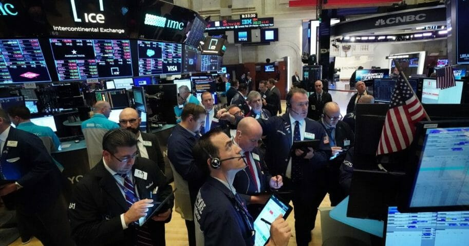 Traders work on the floor at the opening bell of the Dow Industrial Average at the New York Stock Exchange on March 18, 2020, in New York.