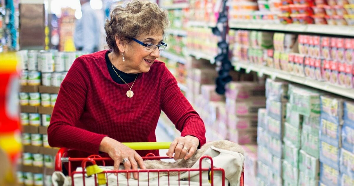 The stock photo above shows a woman shopping at a grocery store.