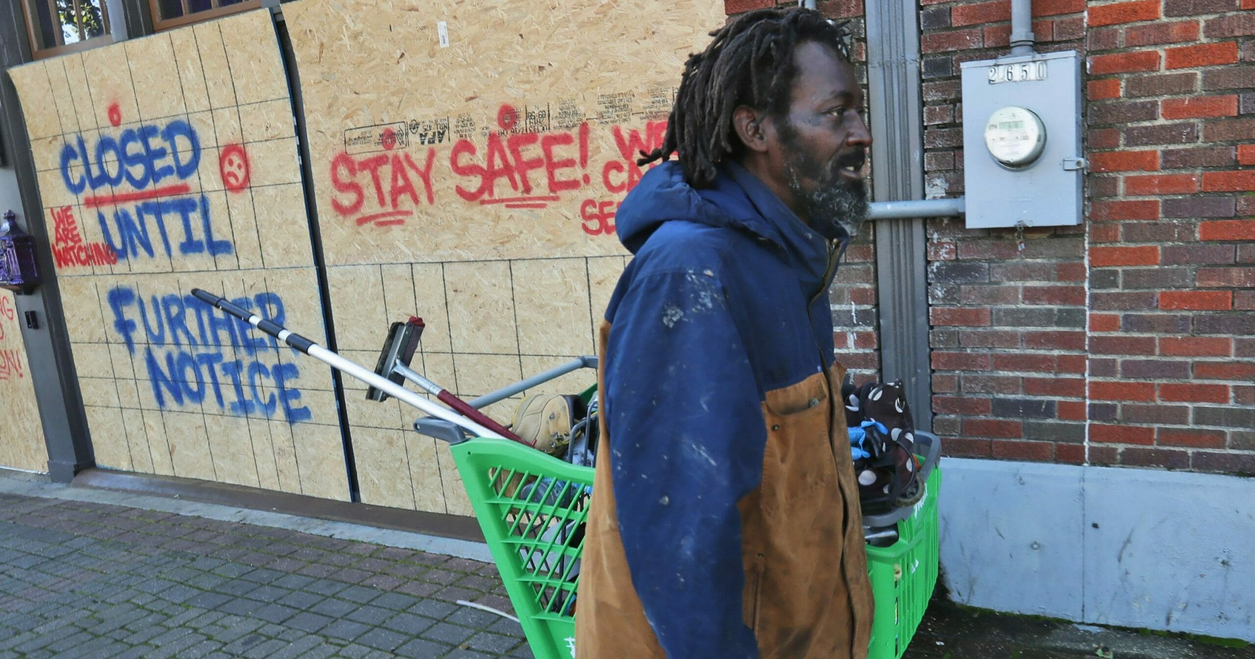 In this March 31, 2020, file photo, Vincent Amos, who identified himself as homeless, pulls a shopping cart with his belongings amid businesses closed by concerns of the COVID-19 coronavirus in the Deep Ellum section of Dallas.