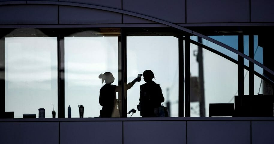 Amid coronavirus concerns, a health care worker takes the temperature of a visitor to Essentia Health in Duluth, Minnesota, who was crossing over a skywalk bridge from the adjoining parking deck April 10, 2020.