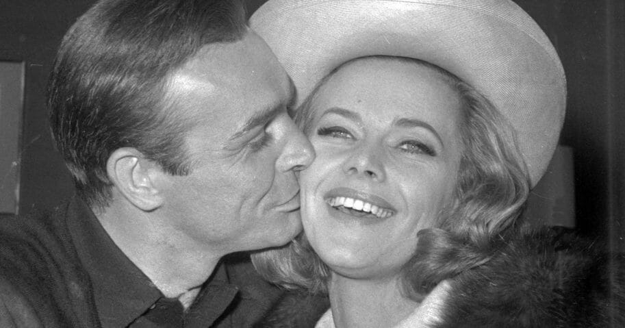 British actor Sean Connery kisses actress Honor Blackman during a party at Pinewood Film Studio, in Iver Heath, England, on March 25, 1964.