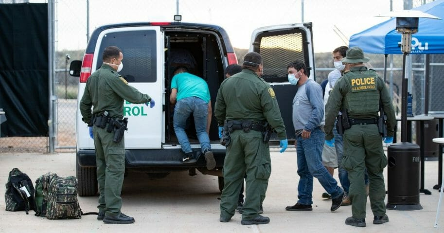 U.S. Border Patrol agents use personal protective equipment as they prepare to transport a group of individuals encountered near Sasabe, Arizona, to the U.S.-Mexico border on March 22, 2020.