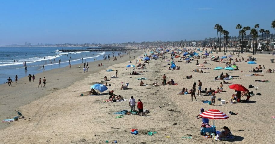 People enjoy the sun, surf and sand north of Newport Beach Pier in California on April 25, 2020.