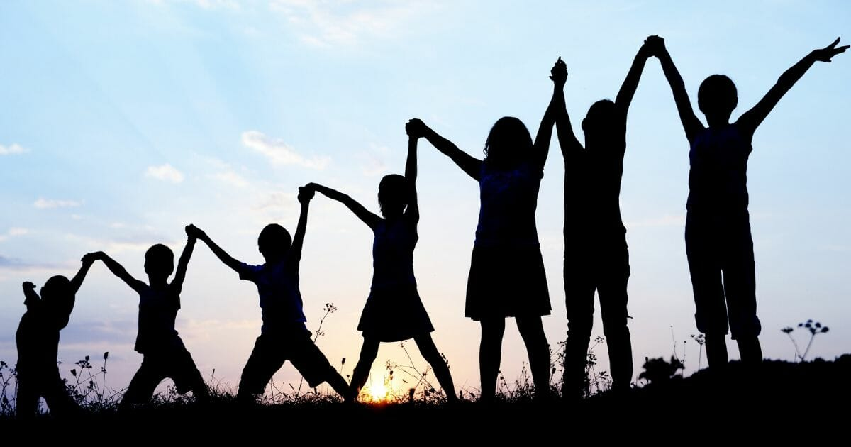 A stock photo of children holding their hands up is seen above.