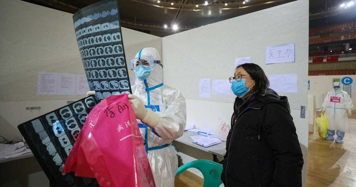This photo taken March 5, 2020, shows a doctor looking at a patient's CT scan at a temporary hospital set up for COVID-19 coronavirus patients in a sports stadium in Wuhan, in China's central Hubei province.