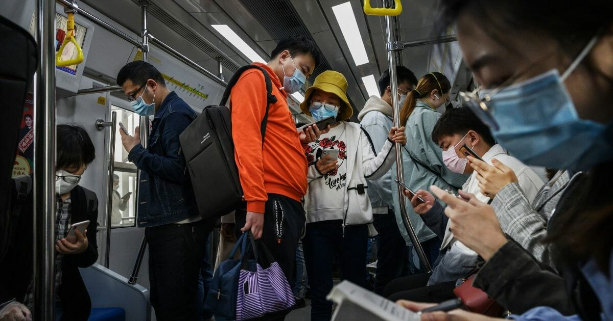 Chinese commuters wear protective masks as they ride the subway during rush hour on April 15, 2020, in Beijing, China.