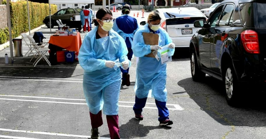 Workers wearing personal protective equipment gather the tests from people's cars administered as Mend Urgent Care conducts drive-thru testing for COVID-19 at the Westfield Fashion Square on April 13, 2020, in the Sherman Oaks neighborhood of Los Angeles, California.