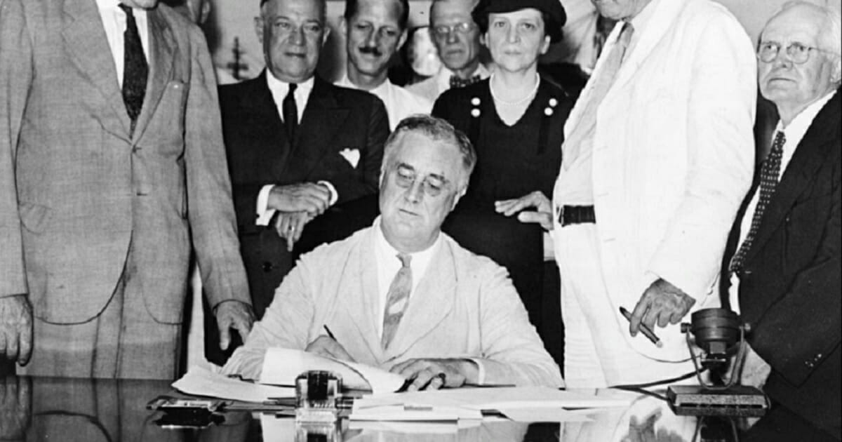 President Franklin Delano Roosevelt signs the Social Security Act in 1937.