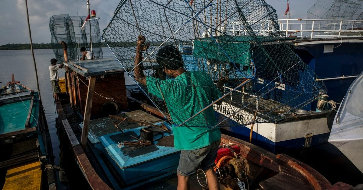 A man carries a trap to his boat in the fishing port of Ranai in Indonesia's Natuna Islands on Aug. 20, 2016.