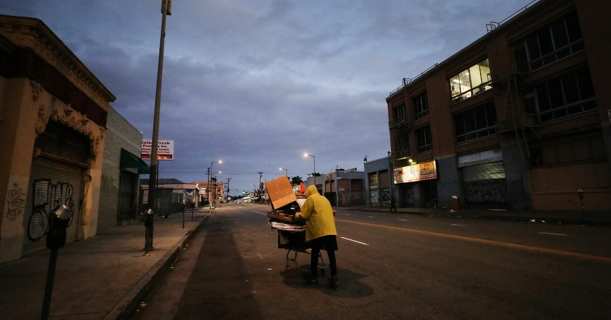 Mal, who is homeless, pushes a cart with his belongings on a street in downtown Los Angeles amid the coronavirus pandemic on April 18, 2020.