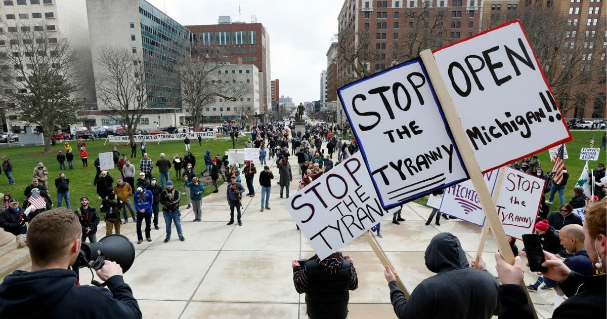 People protest against the government-imposed stay-at-home order quarantine amid the coronavirus pandemic at the Michigan State Capitol in Lansing, Michigan, on April 15, 2020.