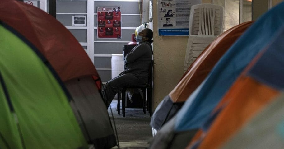 A woman rests near posters with information on the prevention of COVID-19 at the Juventud 2000 migrant shelter in Tijuana, Mexico, on April 3, 2020.