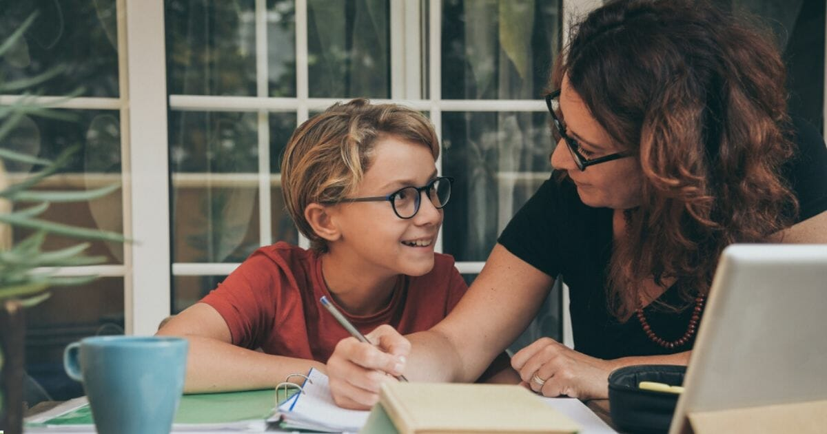 A woman helps a young boy with schoolwork in the stock image above.