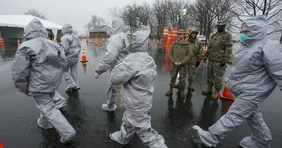 Workers in protective suits get ready while waiting for people to be tested for COVID-19 as they arrive by car at Glen Island Park in New Rochelle, New York, on March 13, 2020.
