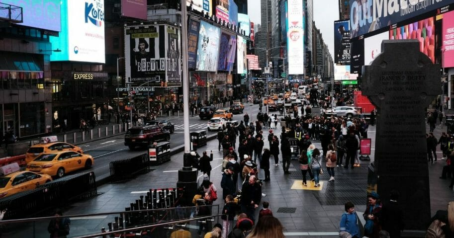 People walk in Times Square in Manhattan, New York on March 12, 2020.