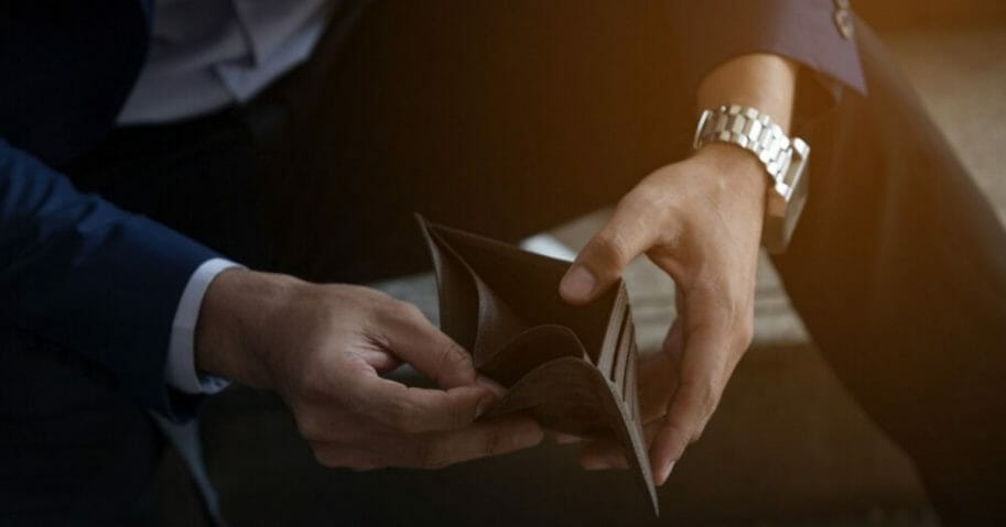 A man looks inside his wallet in the stock photo above.