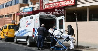 Paramedics transport a patient to the emergency room entrance of the Wyckoff Heights Medical Center in Brooklyn on April 2, 2020, in New York.