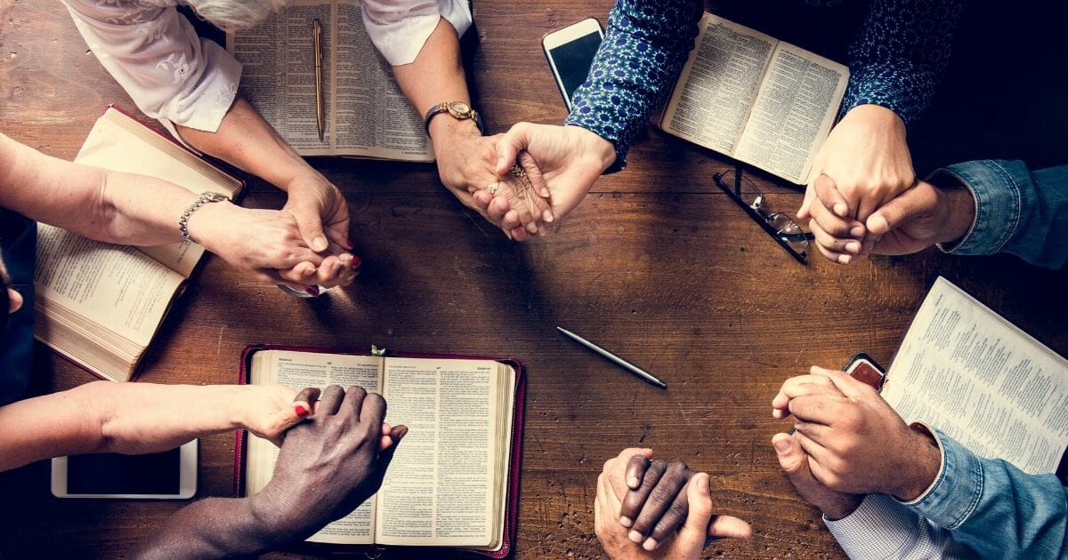 Stock image of a group of people holding hands praying around a table.