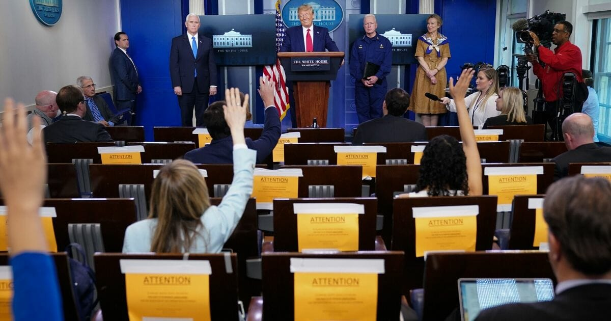 Members of the media raise their hands for questions at the daily coronavirus briefing at the White House on April 6, 2020.