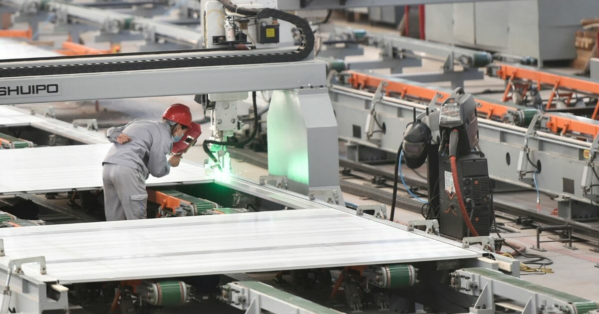 A worker watches over a machine as it welds aluminum at a factory in Zouping in China's Shandong province on March 14, 2020.