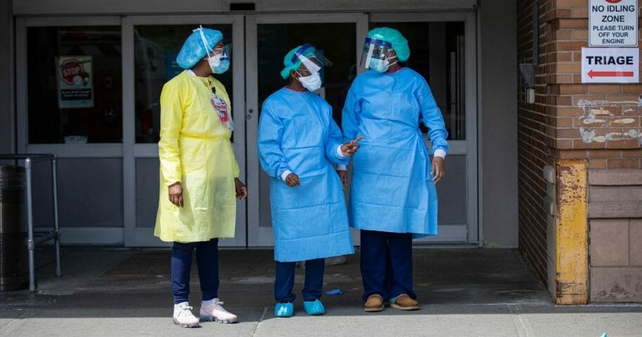 Three emergency room nurses stand outside the Maimonides Medical Center waiting for a midday food delivery on April 7, 2020, in the Brooklyn borough of New York City.