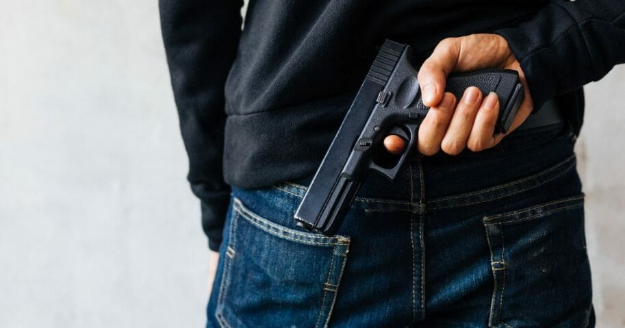 A man's hand holding a gun behind his back.