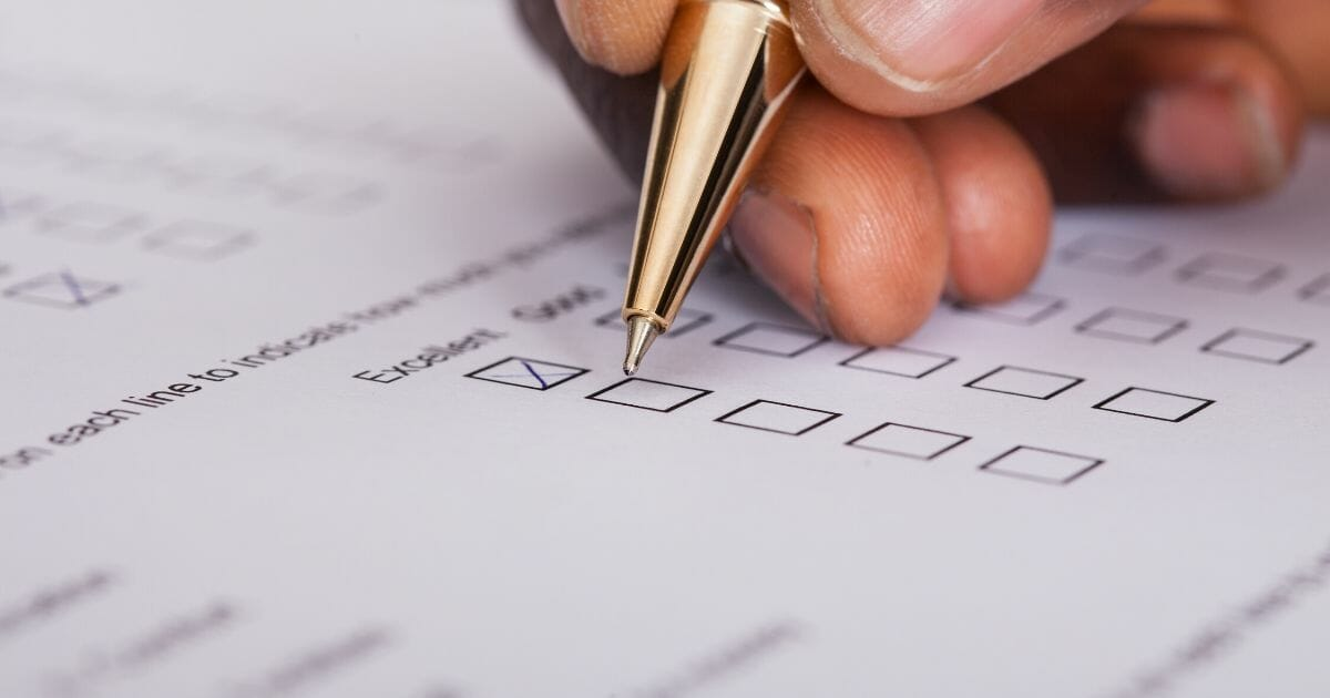 Stock image of a person filling out a survey.